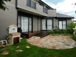 お庭一面に石貼りのステージとスロープ付きのウッドデッキを施工しました。
