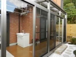 福岡県太宰府市の囲いテラス・サンルーム工事。庭にガラス張りの室内のような癒し空間