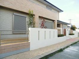 福岡県柳川市の新築外構・低木のある花壇・2トーンの塗り壁・モダンな門扉のクローズ外構