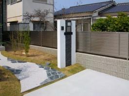 福岡県古賀市の新築外構エクステリア工事。ダークな石とホワイトの門柱。デザイン性の高い門まわり。