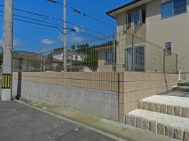 既存ブロック(灰色)の上に化粧ブロックとフェンスを施工しました。
