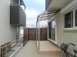 お庭にテラス屋根、タイルポーチ、木目調の背の高いフェンスを施工しました。