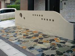玄関前のタイルに沿って施工した門柱と、3種の色をミックスして施工した石張り。