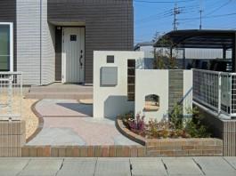 福岡県飯塚市の戸建新築外構工事です。重なりあった門柱と曲がりくねったアプローチの写真です。