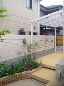 上にはパーゴラ屋根、前には目かくしフェンス、下にはウッドデッキ、隣には花壇のあるガーデン。